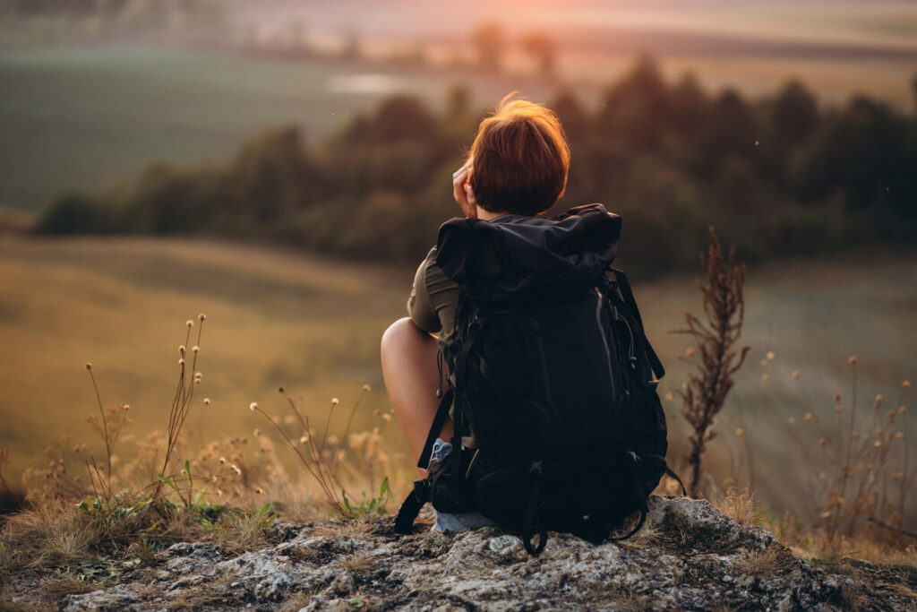 Žena s batohem sedí při západu slunce